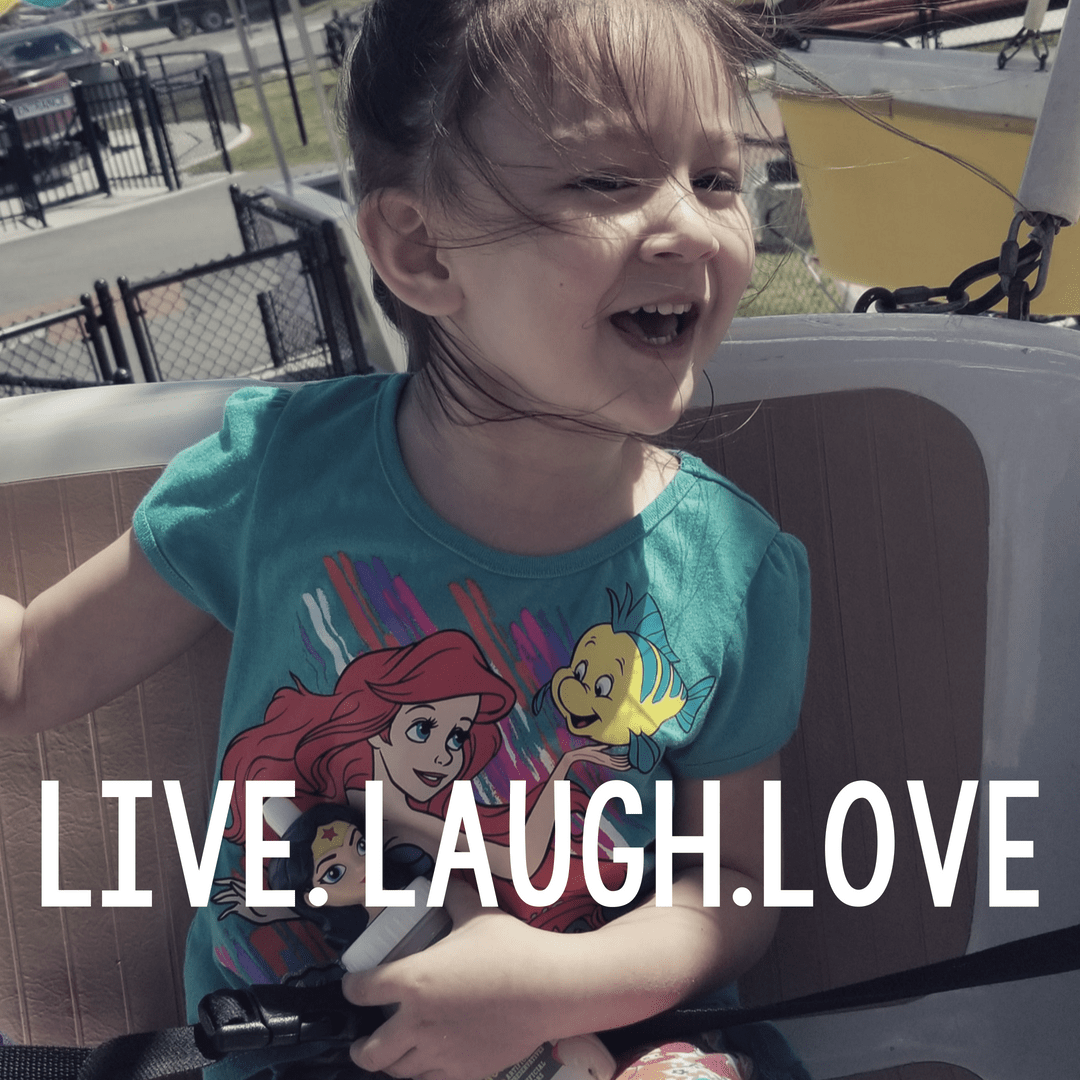 Young girl laughing while on amusement park ride.