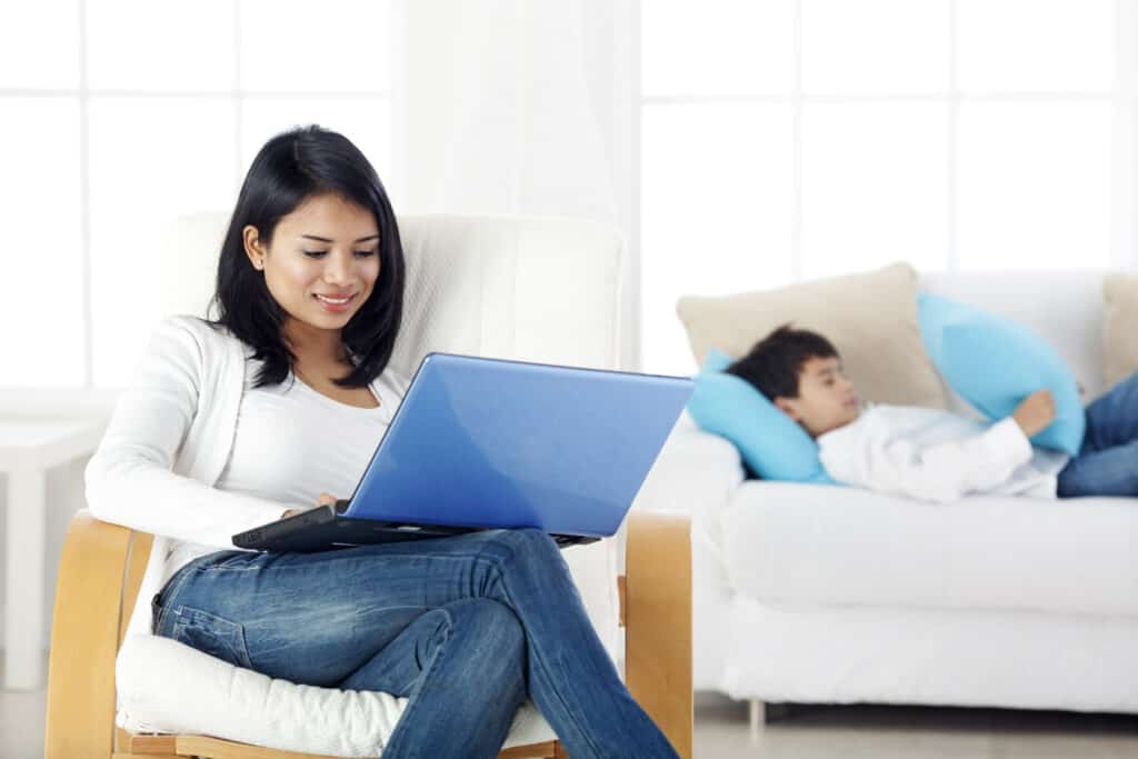 Mother working on laptop at home,  while her child is bored back